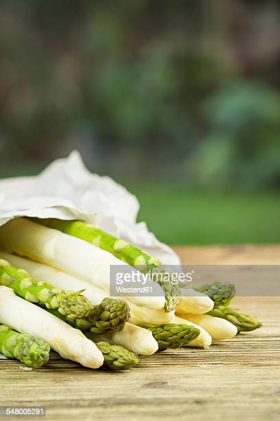 Green and white asparagus on wooden table