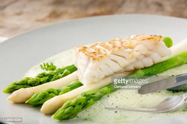 groene en witte asperges met kabeljauw. - bord serviesgoed stockfoto's en -beelden