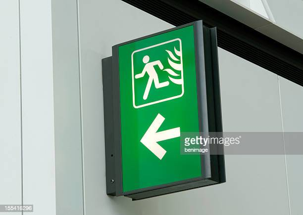 Green and white emergency exit sign on white