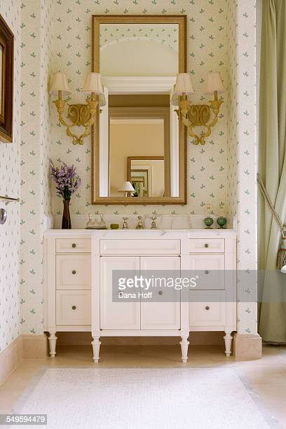green and white wallpapered bathroom with ornate sconces - dana white stock pictures, royalty-free photos & images