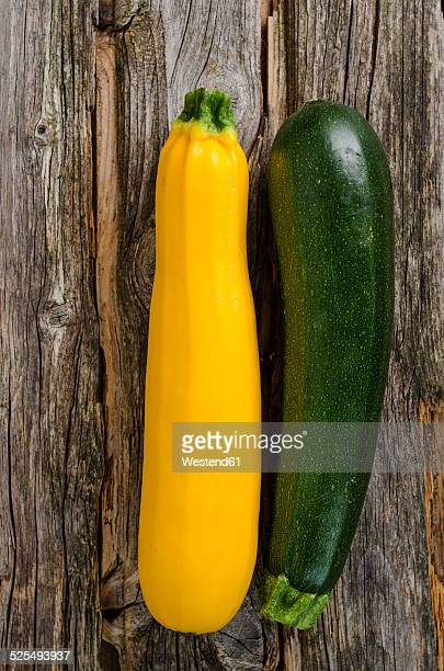 Green and yellow courgettes on wood
