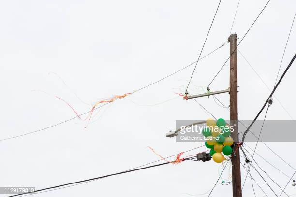 Green and Yellow Helium balloons caught in telephone pole against cloudy sky