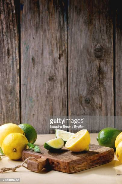 Green And Yellow Lemons With Cutting Board On Table Against Wooden Wall