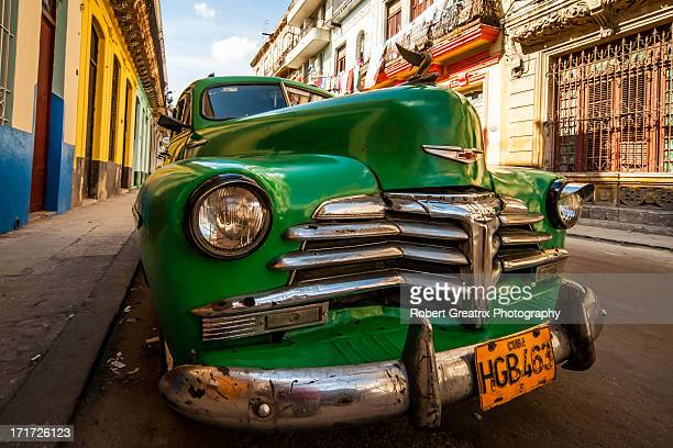 Green Antique car sits on the colourful streets of Havana Centro as a result of the US embargo on Castro's Cuba. A country in change it is still an...