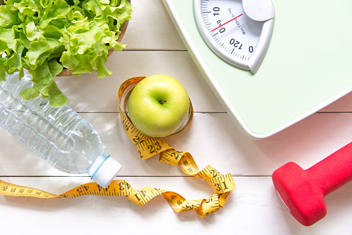 Green apple and Weight scale,measure tap with fresh vegetable, clean water and sport equipment for women diet slimming.  Diet and Healthy Concept 848079198