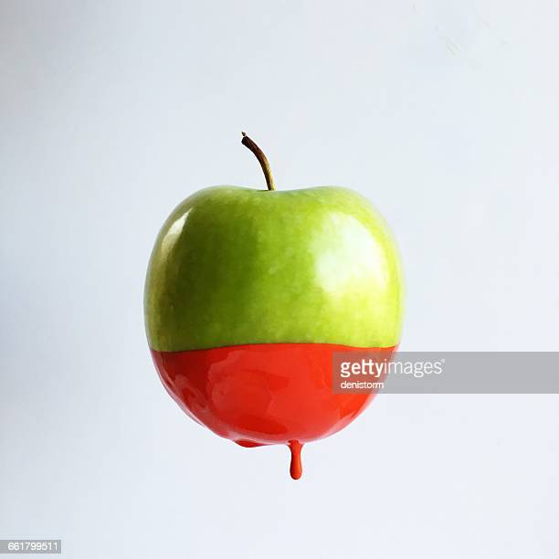 green apple dipped in red paint - chocolate dipped stock pictures, royalty-free photos & images