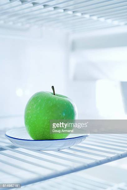 Green apple in an empty fridge