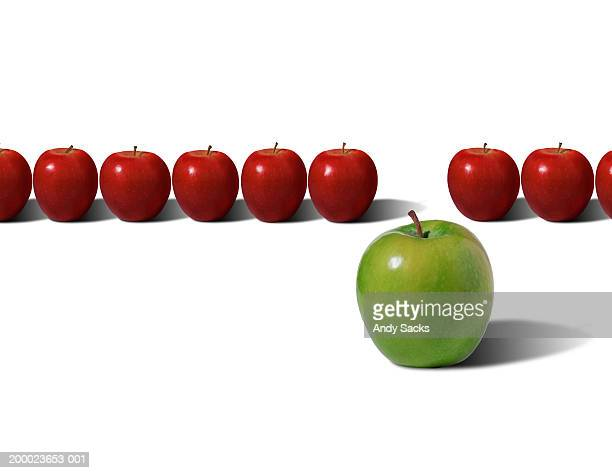 Green apple in front of row of red apples (digital composite)