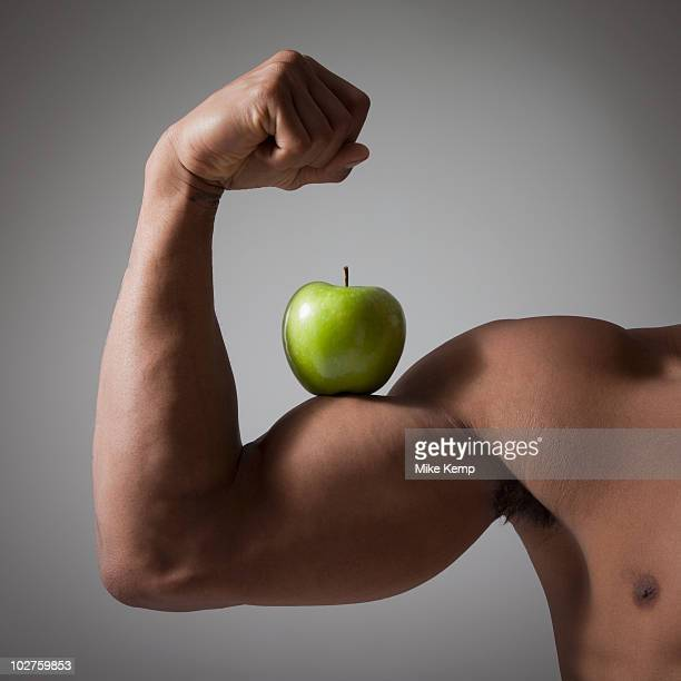 Green apple perched on a flexed muscular arm