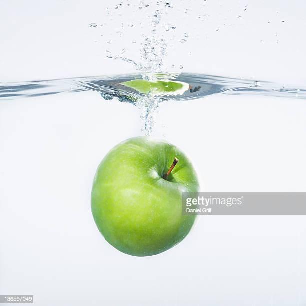 Green apple splashing into water, studio shot