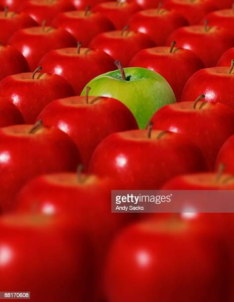 green apple surrounded by red apples - circondare foto e immagini stock
