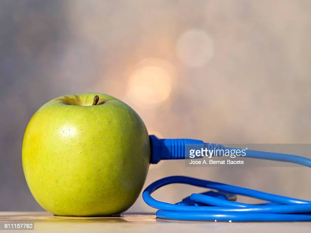 Green apple with an electrical cable connected USB
