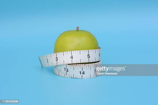 Green apple with measuring tape on blue background, Diet and healthy concept.
