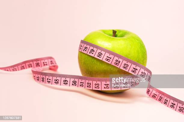 green apple with measuring tape on pink background. - ヤードポンド法 ストックフォトと画像