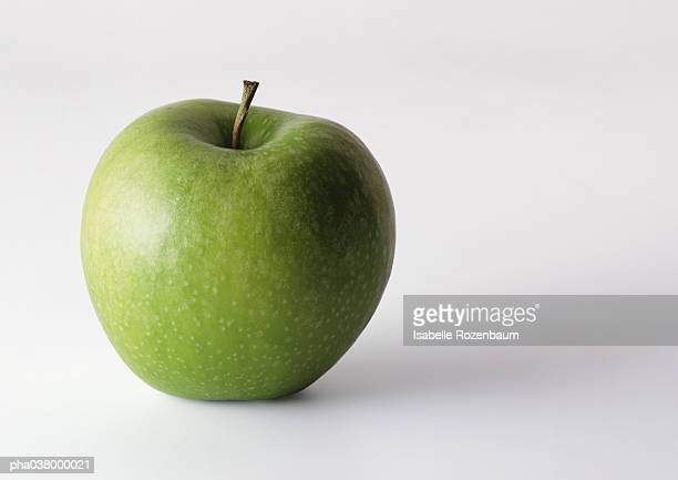Green apple with stem, in upright position, closeup, white background