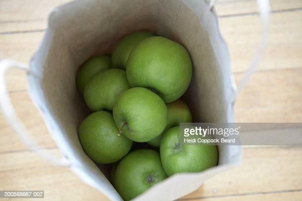 green apples in brown paper bag, overhead view - heidi coppock beard stock-fotos und bilder