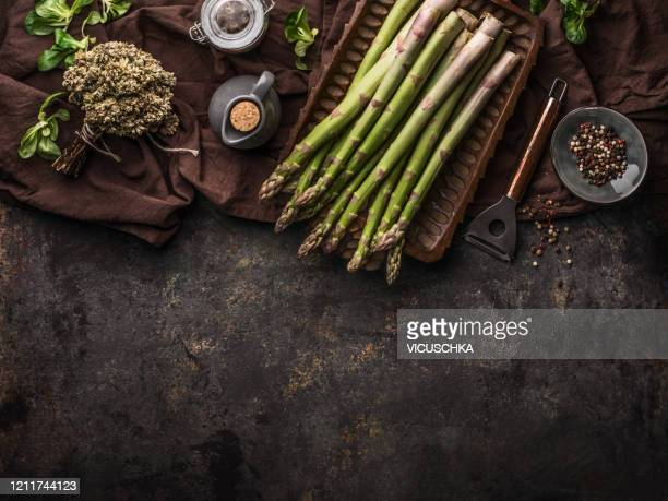 green asparagus bunch on rustic table with copper peeler - asparagus stock pictures, royalty-free photos & images