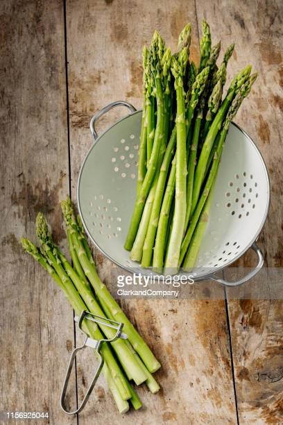 green asparagus in a colander. - asparagus stock pictures, royalty-free photos & images
