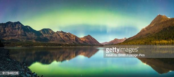 green aurora borealis lights up the night on a clear night at upper trail lake in moose pass, south-central alaska - kenai mountains stock pictures, royalty-free photos & images