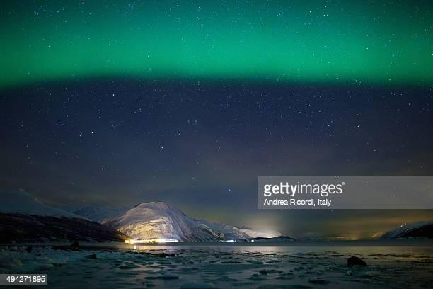 Green aurora borealis over a frozen fjord