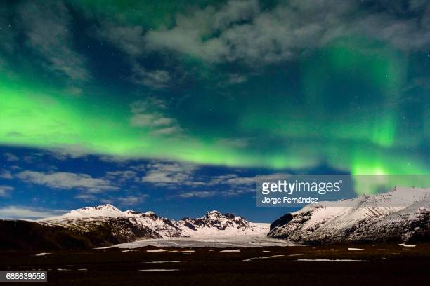 Green auroras over the mountains in the winter skies of Iceland