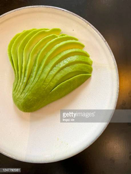green avocado on a white plate - slice stock pictures, royalty-free photos & images