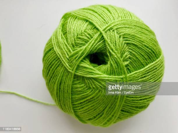 green ball on wool on white background - wool stock pictures, royalty-free photos & images
