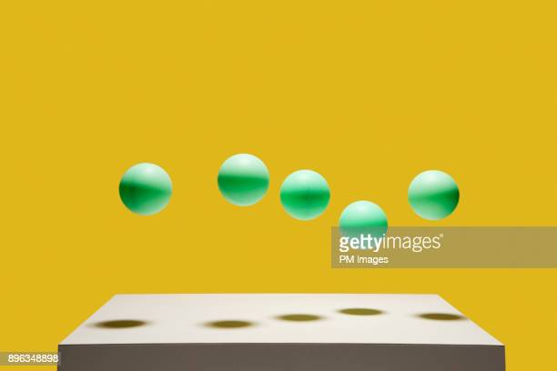 5 green balls bouncing - group of objects stock photos and pictures