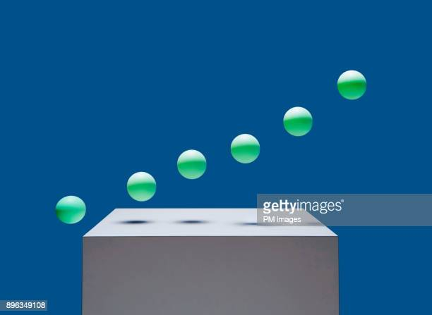 green balls in air over white box - crescimento - fotografias e filmes do acervo