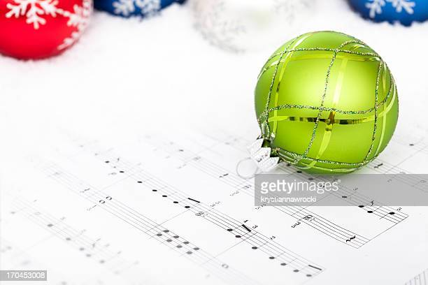 Green Bauble on sheet music with christmas carols