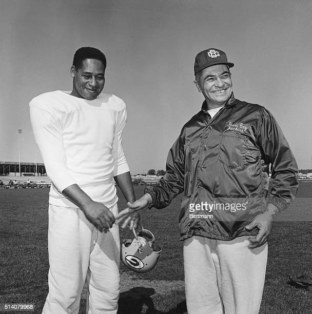 Green Bay Packer defensive back Em Tunnell shakes hands with his coach, Vince Lombardi, on the practice field. Green Bay, Wisconsin, October 27, 1961.