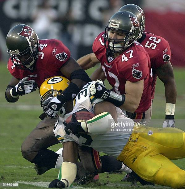 Green Bay Packers Ahman Green is brought down by Tampa Bay Buccaneers Dexter Jackson , John Lynch and Nate Webster , 24 November 2002 during the...