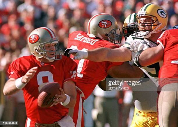 Green Bay Packers defender Matt LaBounty reaches through the offensive line to grab San Francisco 49ers quarterback Steve Young during the first half...