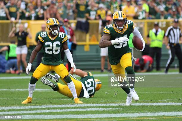 Green Bay Packers defensive back Darnell Savage looks on as Green Bay Packers outside linebacker Preston Smith intercepts a pass during a game...