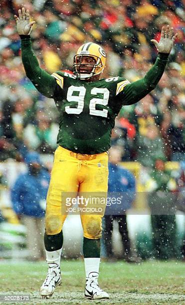 Green Bay Packers defensive end Reggie White raises his hands in acknowledgement of the fans at Lambeau Field during the game with the Tennessee...