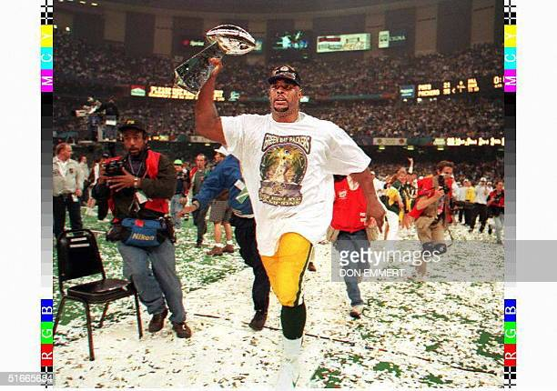 Green Bay Packers defensive tackle Reggie White carries the Vince Lombardi trophy around the field at the Louisiana Superdome after Green Bay won...