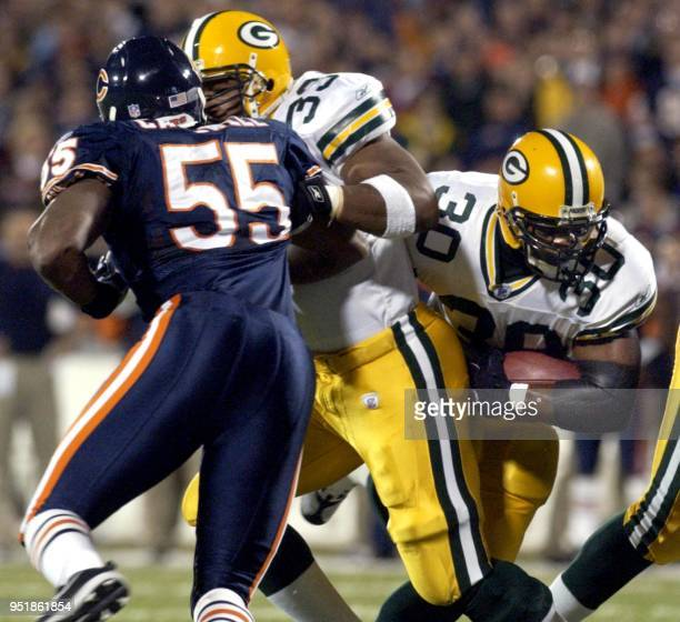 Green Bay Packers fullback William Henderson blocks Chicago Bears linebacker Mike Caldwell opening a hole for Packers running back Ahman Green to...