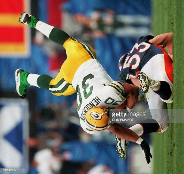 Green Bay Packers fullback William Henderson is upended by Denver Broncos defender Bill Romanowski during first half action at Super Bowl XXXII in...