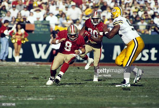 Green Bay Packers Hall of Fame defensive end Reggie White prepares to swat away lead blocker San Francisco 49ers Hall of Fame quarterback Steve Young...