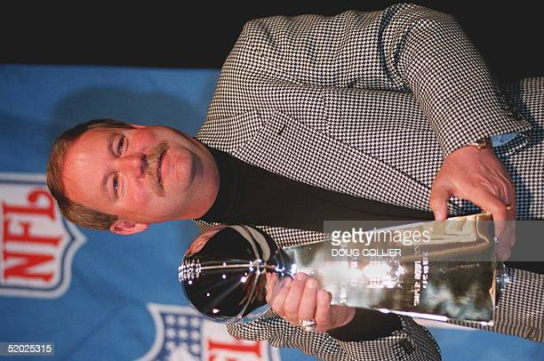 Green Bay Packers' head coach Mike Holmgren poses with the Vince Lombardi trophy 23 January after a press conference for Super Bowl XXXII in San...