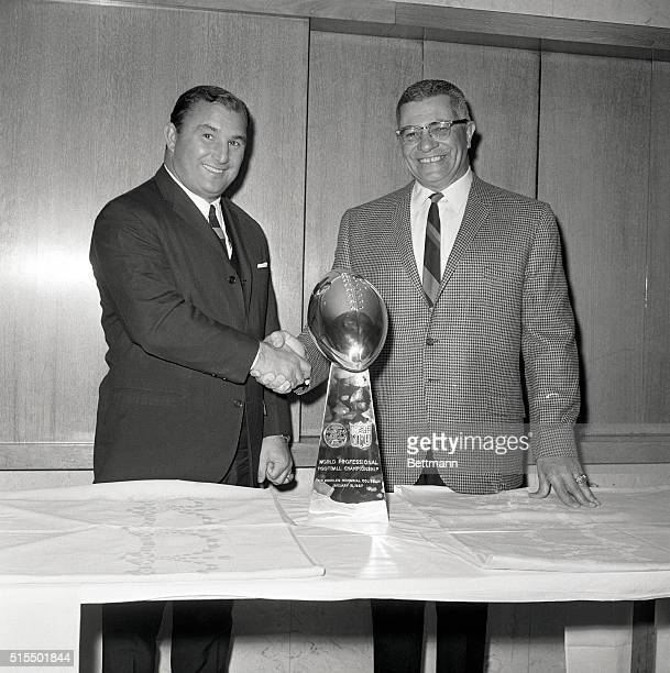 Green Bay Packers head coach Vince Lombardi and Kansas City Chiefs head coach Hank Stram shake hands as they view the Super Bowl Trophy their teams...