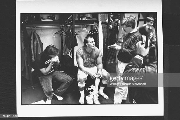 Green Bay Packers offensive lineman Tony Mandarich in uniform sitting on bench preparing to put on his shoes socks as reporter w pad pencil...