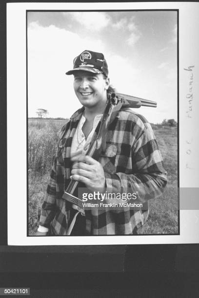 Green Bay Packers offensive lineman Tony Mandarich sporting hunting clothes posing w a doublebarreled shotgun broken open draped over one shoulder at...