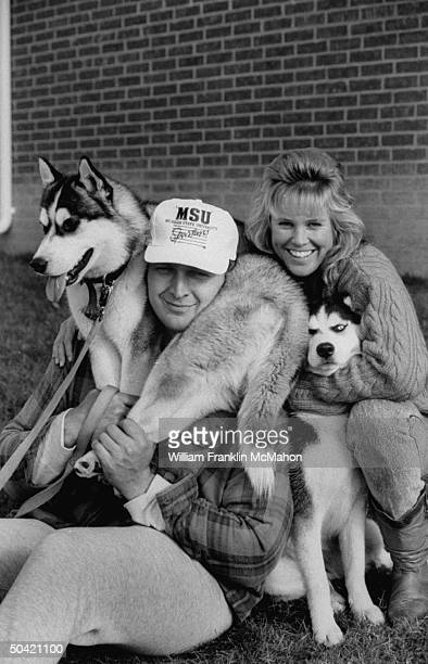 Green Bay Packers offensive lineman Tony Mandarich w one of his Siberian huskie dogs wrapped around his neck as his fiancee Amber Ligon hugs the...