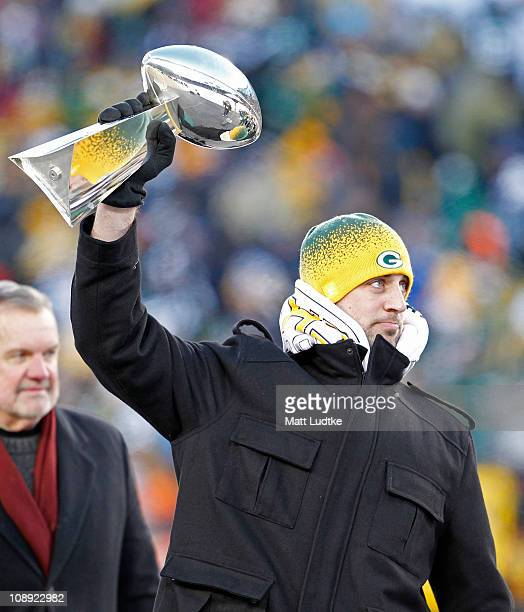 Green Bay Packers quarterback Aaron Rodgers hoists the Lombardi Trophy during the Packers victory ceremony at Lambeau Field on February 8 2011 in...
