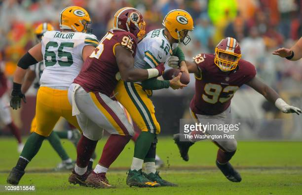 Green Bay Packers quarterback Aaron Rodgers is sacked by Washington Redskins defensive tackle Da'Ron Payne left as Washington Redskins defensive end...