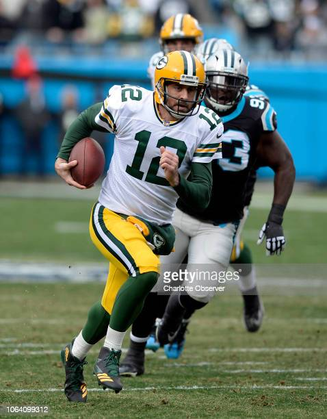 Green Bay Packers quarterback Aaron Rodgers runs past Carolina Panthers defensive end Kyle Love in the first half on Sunday Dec 17 2017 at Bank of...
