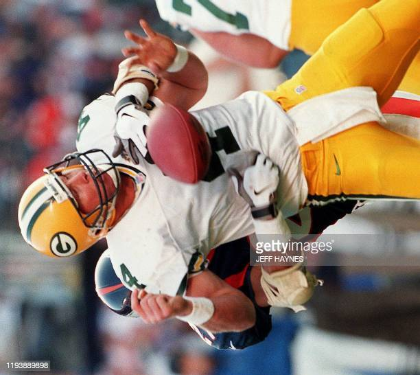 Green Bay Packers quarterback Brett Favre loses the ball as he is sacked by Denver Broncos defender Steve Atwater in the first half of Super Bowl...