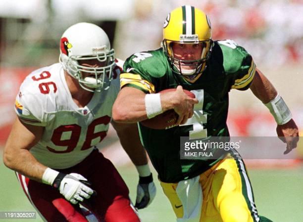 Green Bay Packers' quarterback Brett Favre scrambles away from Arizona Cardinals defensive end David Bowens during the second quarter 24 September...