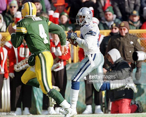 Green Bay Packers quarterback Brett Favre watches as Dallas Cowboys corner back Deion Sanders returns an interception fifty yards for a touchdown in...